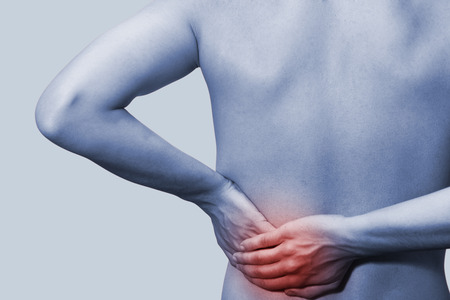 malady: Young male holding his back in pain. On a blue background