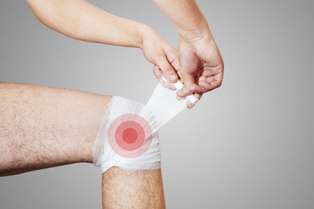 malady: The young man keeps for leg. The bandage on a grey background