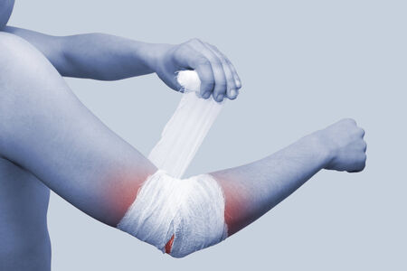 elbow band: The young man keeps for hand. The bandage on a blue background