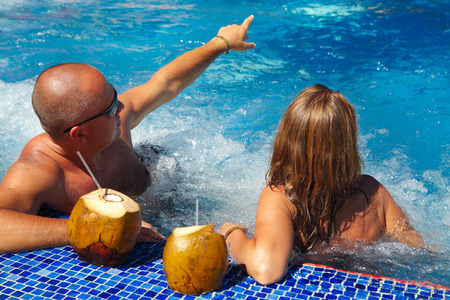 water hottub: Romantic couple with coconut drink relaxing in hot tub. Stock Photo