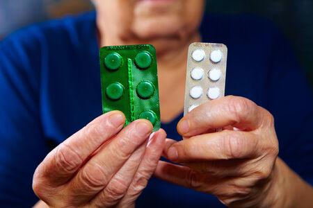pilule: Manos de mujer de edad avanzada con las p�ldoras. Fondo Farmac�utica Foto de archivo