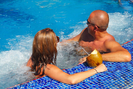 water hottub: Couple with coconut drink relaxing in hot tub.