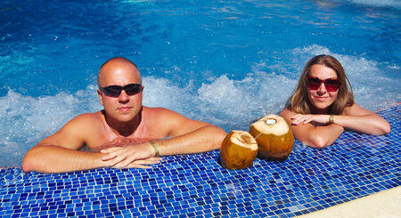 Couple with coconut drink relaxing in hot tub. photo