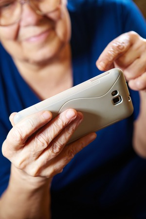 Elderly woman with a smartphone. Senior people using internet photo