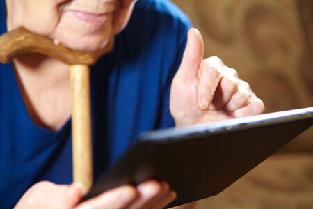 Elderly woman with tablet computer. Senior people using internet photo