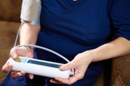 diastolic: Senior woman measuring blood pressure. Health care background