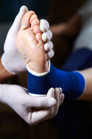 Doctor doing a bandage for patient. First aid photo