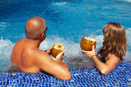 Couple with coconut drink relaxing in hot tub.