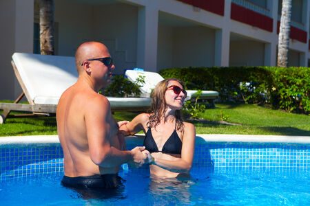 Loving happy couple in pool. Summer vacation. photo