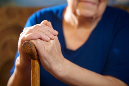 Old woman hands with cane. Senior people health care.