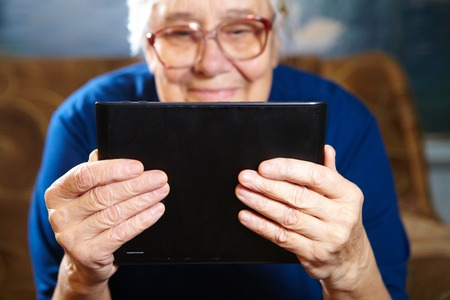 old cell phone: Elderly woman with tablet computer. Senior people using internet