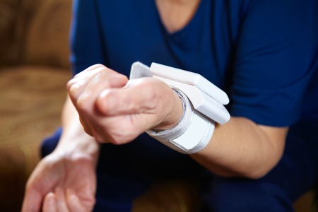 hypotension: Senior woman measuring blood pressure. Health care background