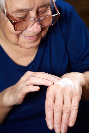 aging woman: Senior woman with anti aging cream for hands Stock Photo