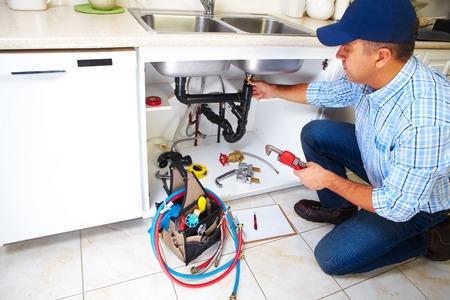 ca�er�as: Fontanero con herramientas de fontaner�a en la cocina. Renovaci�n.