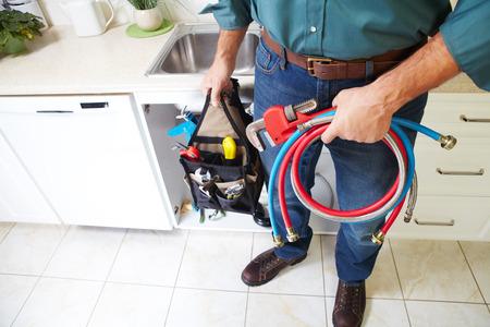 plumbing tools: Plumber with Plumbing tools on the kitchen. Renovation.