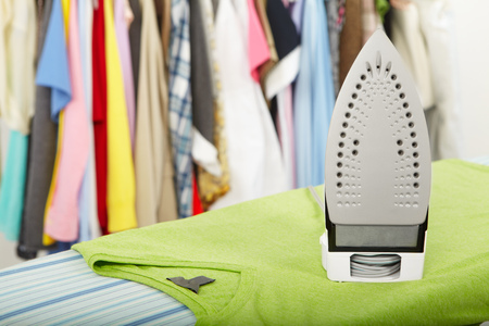 Electric iron and shirt, on cloth background