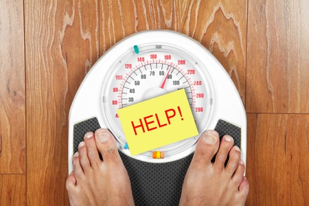 scales thin: Closeup of mans feet on weight scale indicating overweight