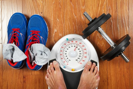 low scale: Closeup of mans feet on weight scale indicating overweight