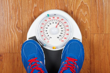 low scale: Closeup of man feet on weight scale indicating overweight