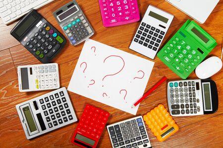 calculadora: Signo de interrogaci�n y calculadoras que mienten en el suelo de madera Foto de archivo