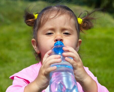 girlie: Child drinks water on a green lawn