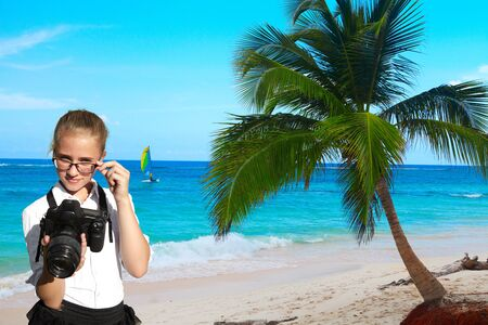 reflex camera: Young girl, reflex camera and tropical palm on blue sky background. Exotic vacation