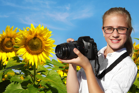 reflex camera: Young girl, reflex camera and field of blooming sunflowers