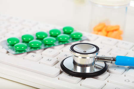 medicament: Stethoscope on the keyboard. Medicament and pills