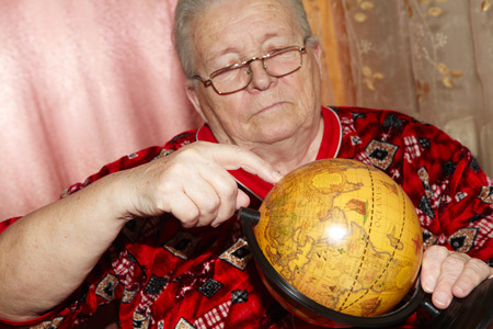 geography: Elderly woman and terrestrial globe. Senior people and geography