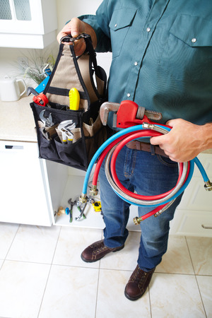kitchen renovation: Plumber with Plumbing tools on the kitchen. Renovation.