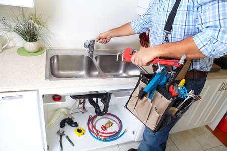 plumbing tools: Plumber on the kitchen. Renovation  and plumbing.