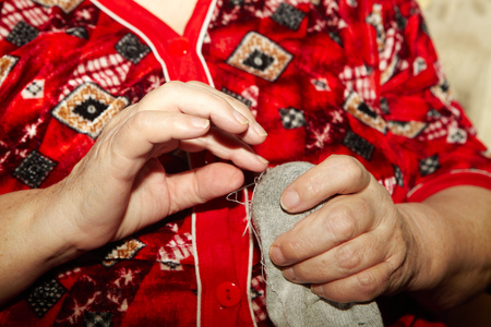 darn: Old woman to sew over a tear