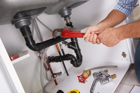 Plumber with Plumbing tools on the kitchen. Renovation.