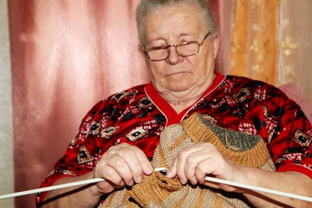 old people: Old woman and knitting sweater. Senior people