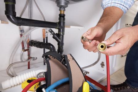 cañerías: Fontanero con herramientas de fontanería en la cocina. Renovación.