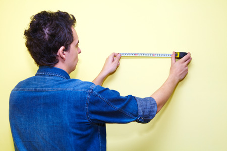 plasterer: Mature contractor plasterer working indoors in yellow room Stock Photo