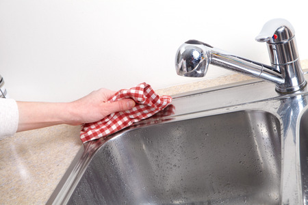 doing chores: Woman hand doing chores in the kitchen at home , cleaning sink and faucet Stock Photo