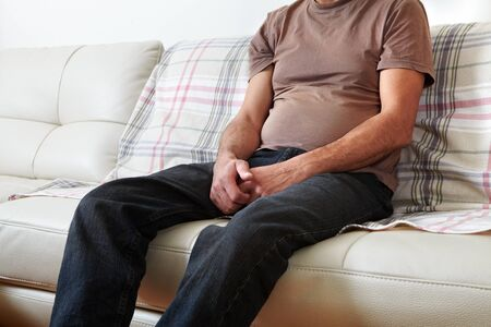 suffering: Unhappy man suffering from backache at home