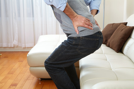 Unhappy man suffering from backache at home