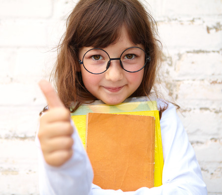 white walls: Little girl with glasses holding a books in their hands Stock Photo