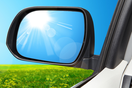 rearview: Reflection sun at the rear-view mirror on a modern car
