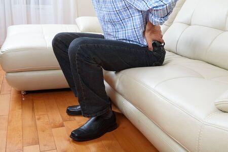 nephritis: Unhappy man suffering from backache at home