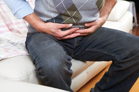 appendicitis: Unhappy man suffering from belly-ache at home