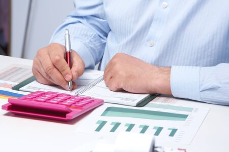 place of employment: Businessman working with calculator in the office