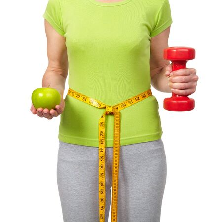 Woman with a dumbbells and apple. Isolated white background