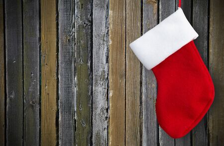 Red christmas sock hanging on brown wooden wall