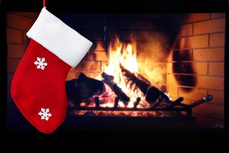 Red christmas sock and fireplace in the room. Christmas