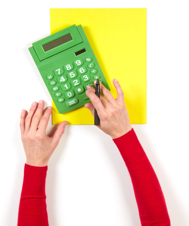 computation: Hands with green calculator and yellow sheet of paper