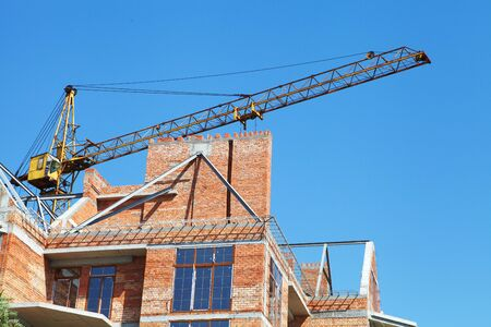 Building crane and building under construction and blue sky