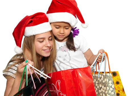 Two little girls in fur-cap with shopping bags. Isolated over white background. Christmas